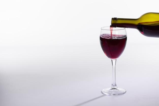 레드 와인 병은 복사 공간이 있는 흰색 배경에 유리를 붓습니다.