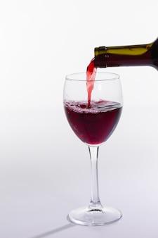 레드 와인 병 흰색 배경에 유리를 붓는