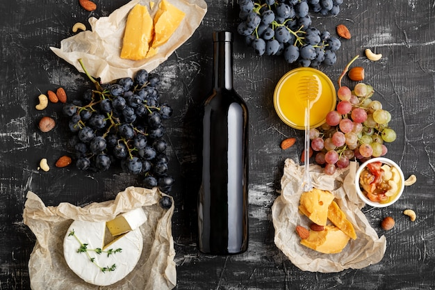 Red wine bottle wine and food composition gastronomy ingredients different cheese grapes
