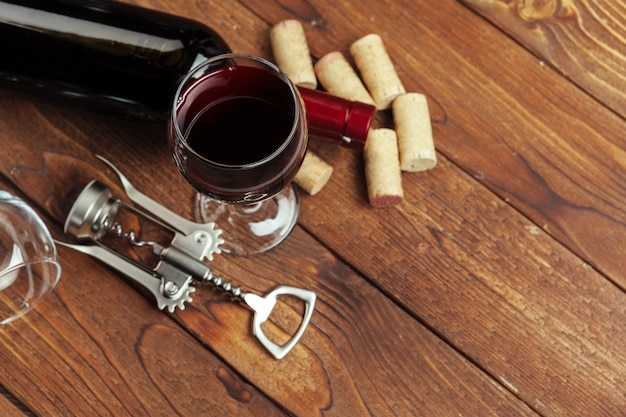 Red wine bottle, wine glass and corkscrew