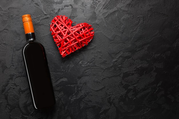 Red wine bottle with wicker decorative heart on black stone table.