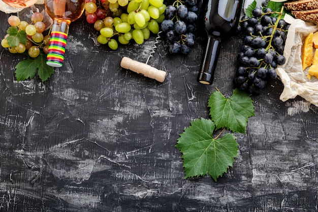 Red wine in bottles cheese grapes with vine plant on dark concrete background