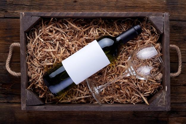 開いた木製の箱に詰められた赤ワインのボトル