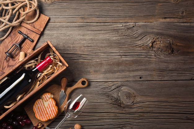 Red wine in a box with a glass, corkscrew and cream cheese on a wooden old table. top view with space for your greetings.