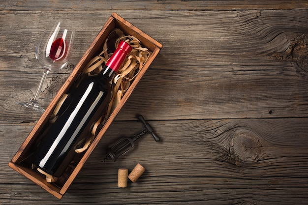 Red wine in a box with a glass and a corkscrew on a wooden table. top view with space for your greetings