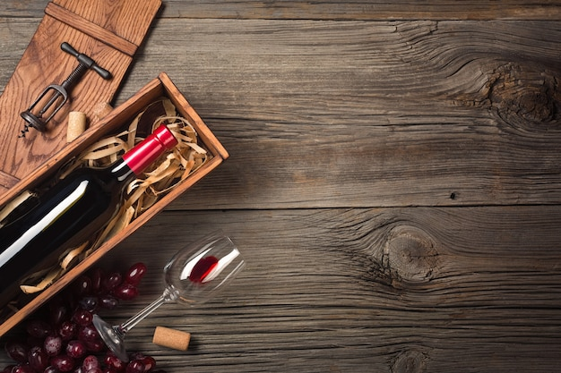 Red wine in a box with a glass and a corkscrew on a wooden table. top view with space for your greetings.