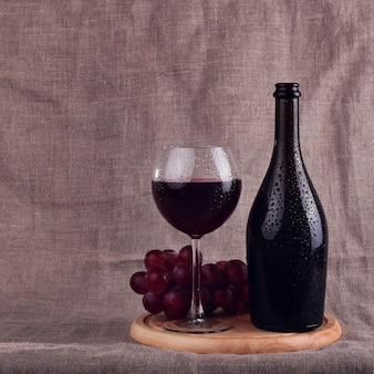 Red wine, cheeses and grapes in a still life setup.