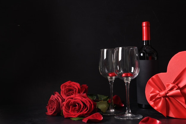 Red wine, chocolate sweets, roses with gift for valentine's day