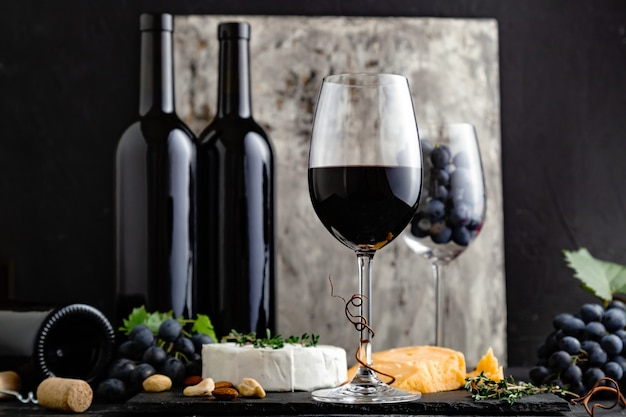 Red wine in classic glass with wine bottles composition. elegant wine bar menu with snacks cheese on dark moody background.vintage red wine on black gray concrete background.