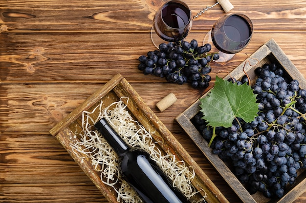 Red wine composition on brown wooden table. top view. red wine bottle corkscrew corks wine glasses black ripe grapes in box on wooden table. flat lay copy space.