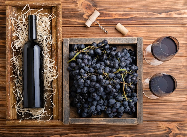 Red wine composition on brown wooden table. top view. red wine bottle corkscrew corks wine glasses black ripe grapes in box on wooden table.