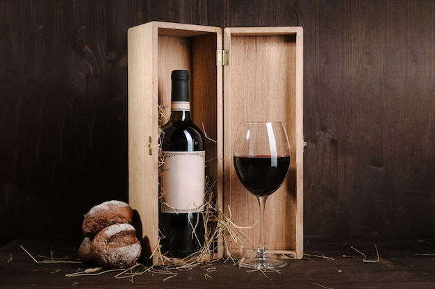 Red wine composition with bread bottle in box and wineglass on brown wooden table