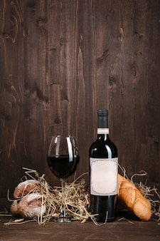 Red wine composition with bread bottle and wineglass on brown wooden table