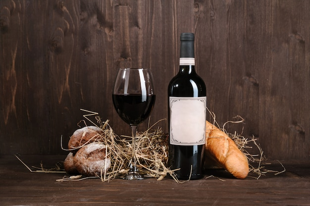Red wine composition with bread bottle and wineglass on wooden table