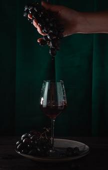 Красное вино капает с виноградной лозы в бокал. темный фон, вертикальное фото.