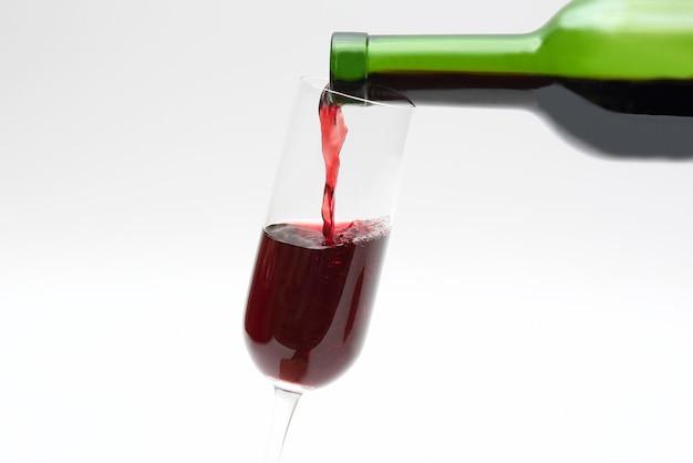 緑の瓶から赤ワインをグラスに注ぐ