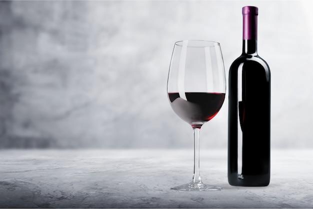 Бокал для красного вина и бутл с тенью на фоне