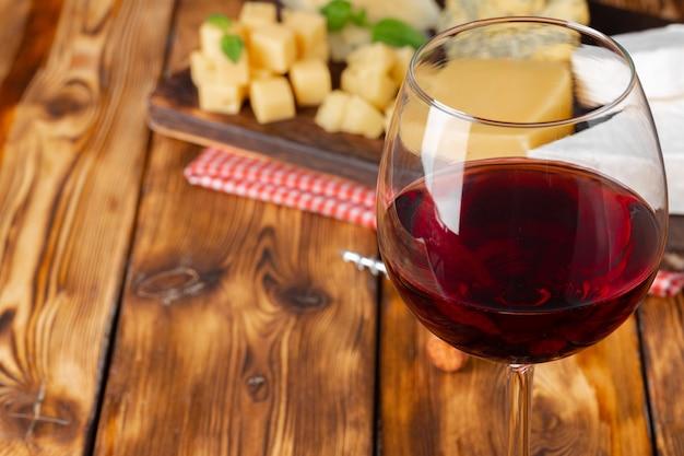 Бокал красного вина и сырные блоки на деревянном столе крупным планом