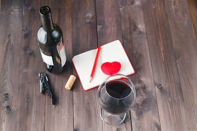 赤ワインのグラスとテーブルの上のノート