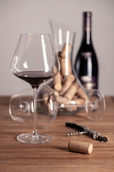 Red wine glass, bottle, corkscrew, decanter, corks on wooden table