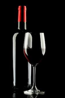 Red wine glass and bottle silhouette on black background
