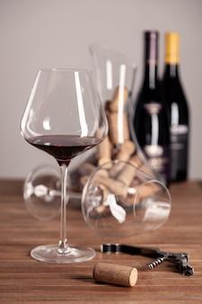 Red wine glass, bottles, corkscrew, decanter, corks on wooden table