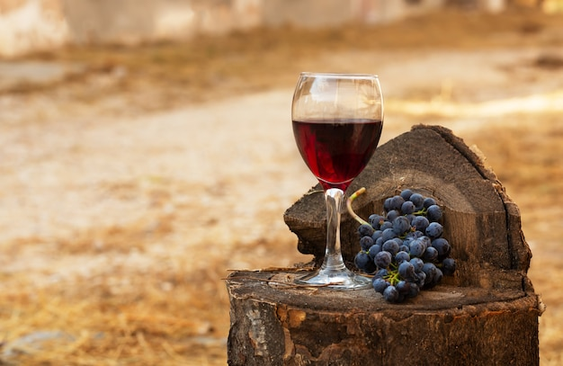 Red wine glass and bunch of grapes on a old wooden background.