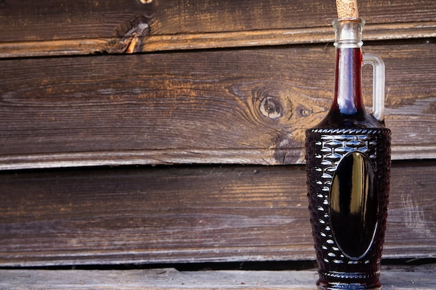 Red wine in glass carafe on wooden background