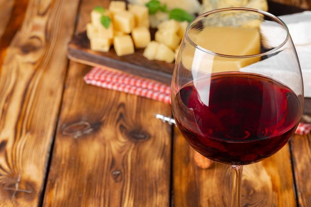 Red wine glass and cheese blocks on wooden table close up