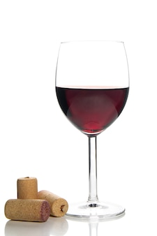 Red wine glass and corks on white