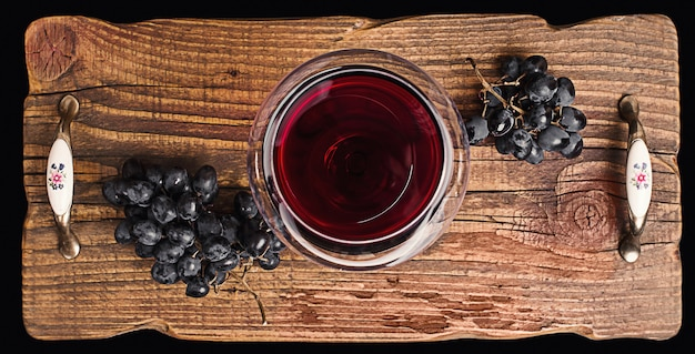 Red wine in a glass and ripe grapes on rustic textured wooden tray.