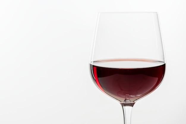 Vino rosso in un bicchiere su sfondo bianco