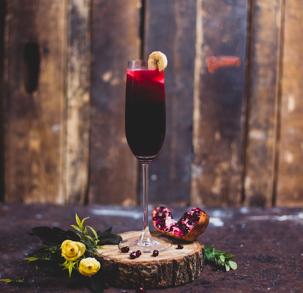 Red wine glass with a slice of banana on a piece of wood with granate. rustic background