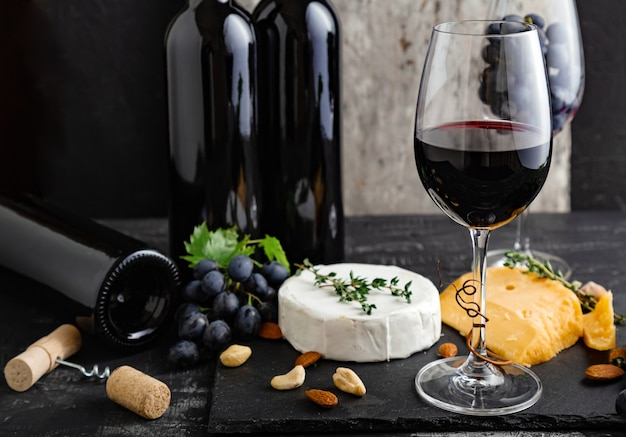 Red wine glass with wine bottles composition. wine bar with cheese plate on dark moody background.