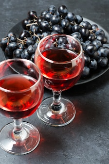 Red wine in glasses, a bunch of black grapes