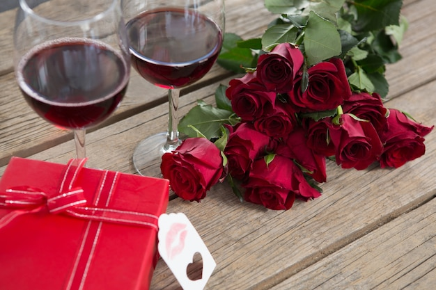 Red wine glasses, gift and roses on wooden surface