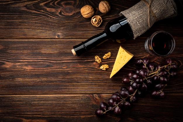 Красное вино, виноград, сыр и грецкий орех на темном деревянном фоне.