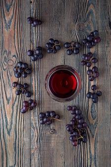 Красное вино в бокале и виноград на старый деревянный стол. вид сверху.