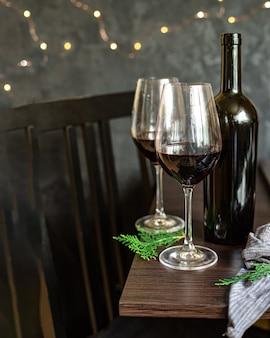 ガラスのお祝いのクリスマスホリデーパーティー新年の食事の赤ワイン