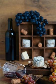 Красное вино в бокале рядом с сыром и виноградом
