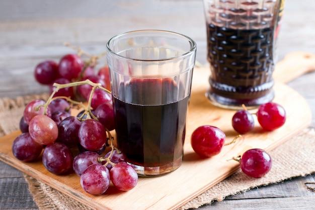 古いテーブルの上にブドウとグラスの赤ワイン
