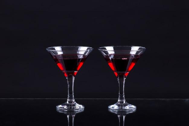 Красное вино в двух бокалах мартини на черном фоне