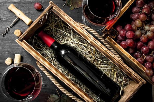 검은 칠판에 코르크와 오래 된 상자에 레드 와인.