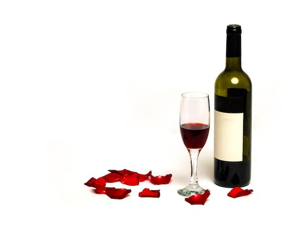 꽃 꽃잎으로 장식 된 흰색 배경에 고립 된 병 크리스탈 유리에 레드 와인. 신년 장식 크리스마스, 크리스마스, 신년 파티. 와인 글라스와 알코올 한 잔