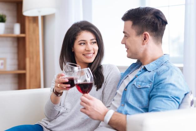 赤ワイン。笑顔でワインとグラスをチリンと鳴らす楽観的なカップルに触発された