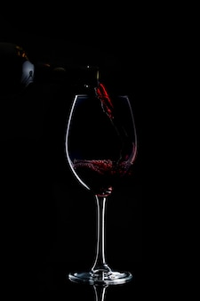 Red wine is being poured to glass with long stem in dark