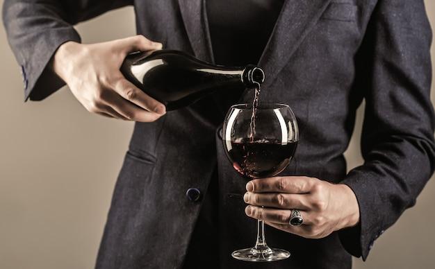 Красное вино переливается из бутылки в бокал. бутылка для напитков для гурманов, бокал для красного вина,