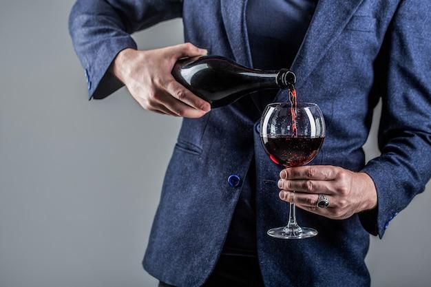 Красное вино переливается из бутылки в бокал