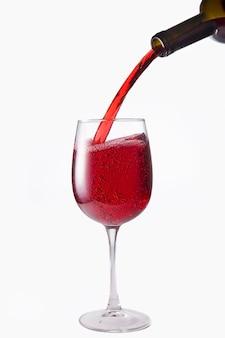 Красное вино наливают в бокал из бутылки, выделяют на белом фоне