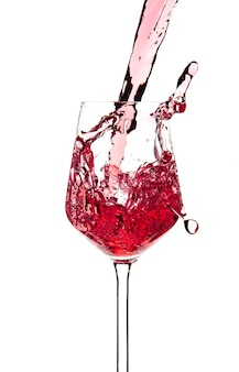 Red wine is pouring into a glass goblet on a white background. alcoholic drinks. high quality photo